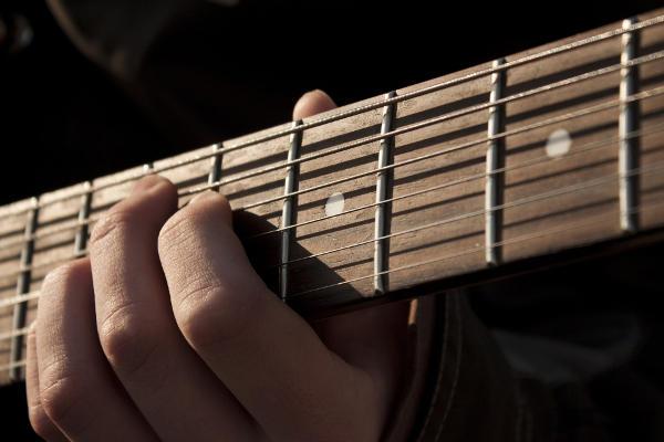 Dłoń człowieka grającego na gitarze akustycznej