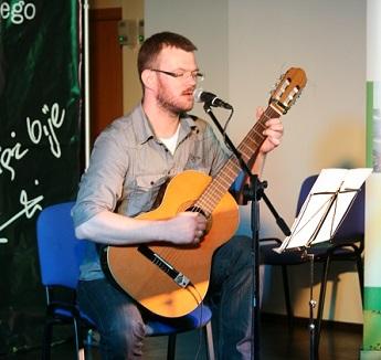 Mężczyzna w okularach, z lekkim zarostem na twarzy, młody gra na gitarze, śpiewa.