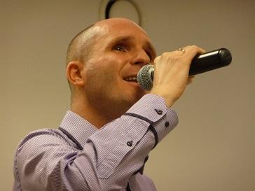 Na zdjęciu młody mężczyzna śpiewa.