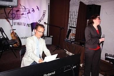 Na zdjęciu młody mężczyzna gra na pianinie cyfrowym, obok stoi młoda kobieta w okularach z mikrofonem w dłoni.