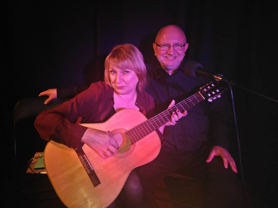 Kobieta gra na gitarze, za nią mężczyzna w średnim wieku. Uśmiechają się.