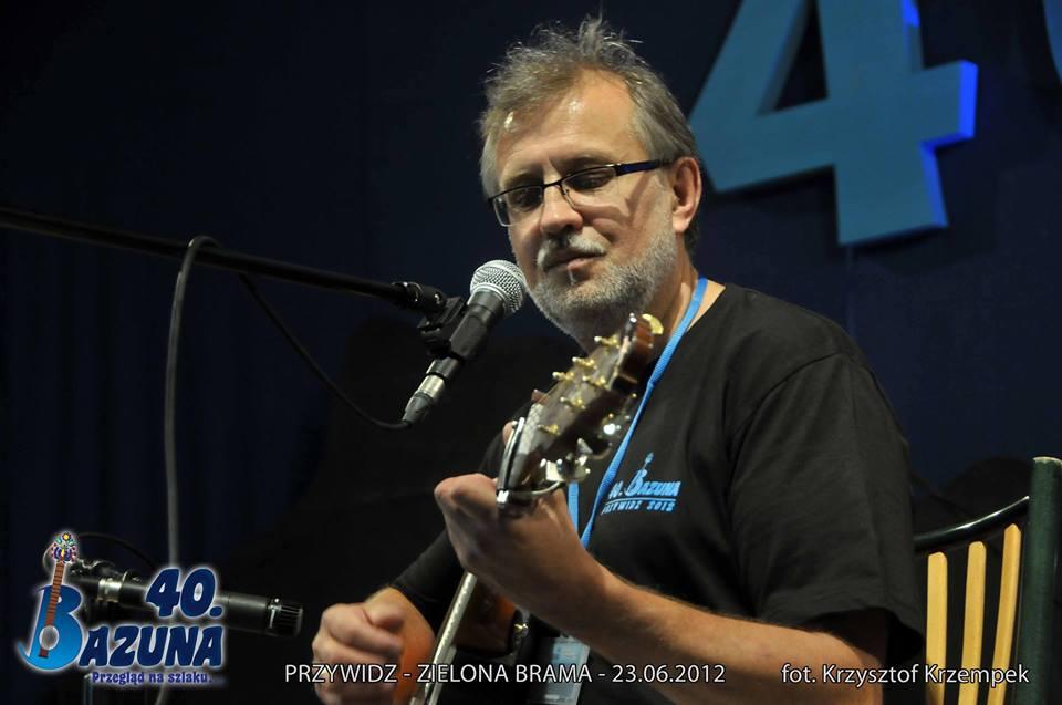 Mężczyzna w średnim wieku, w okularach gra na gitarze.
