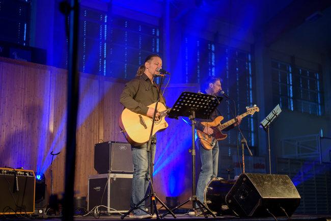 Dwóch mężczyzn na scenie, grają na gitarach.