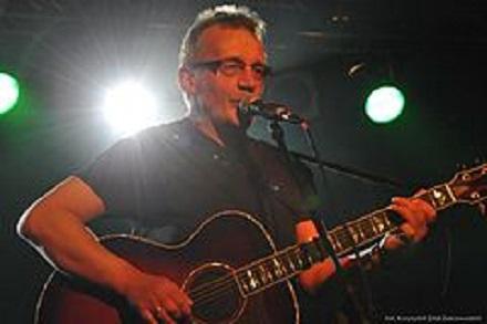 Mężczyzna w średnim wieku, na scenie, gra na gitarze.