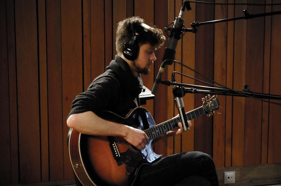 Młody mężczyzna, na scenie, w łuchawkach, gra na gitarze klasycznej.