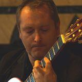 Na zdjęciu mężczyzna w skupieniu gra na gitarze klasycznej.