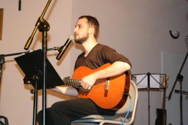 Młody mężczyzna na scenie, gra na gitarze.