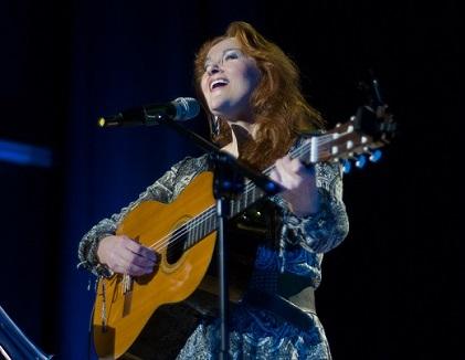 Długowłosa kobieta na scenie, gra na gitarze klasycznej.