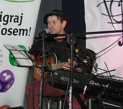 mężczyzna w kapeluszu gra na gitarze