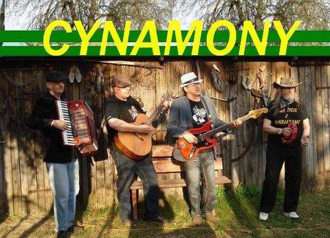 Na zdjęciu czterech mężczyzn w średnim wieku, dwóch z gitarami, jeden z akordeonem, jeden z banjo. Na górze wielki napis Cynamony