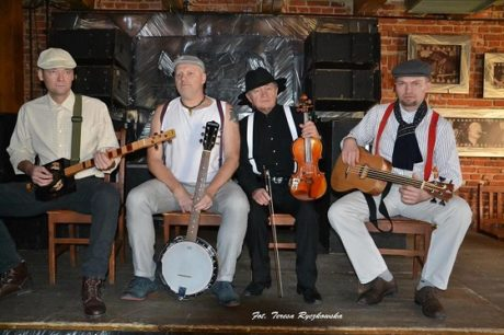 Czterech muzyków siedzi na scenie , dwóch z gitarami, jeden ze skrzypcami, jeden z banjo.