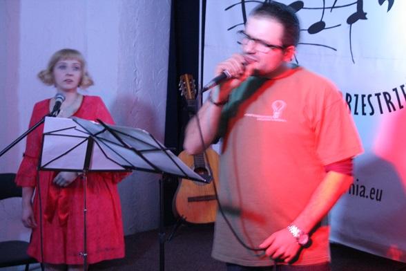 Na zdjęciu młoda kobieta w czerwonej sukience patrzy na śpiewającego, młodego mężczyznę.