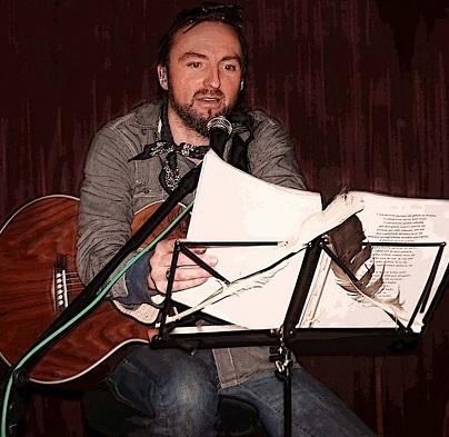 Na zdjęciu młody mężczyzna, gra na gitarze i śpiewa.