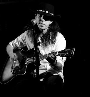 Młody mężczyzna w kapeluszu, gra na gitarze.