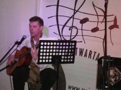 Na zdjęciu młody mężczyzna na scenie gra na gitarze, śpiewa. W tle logo Światłowni.