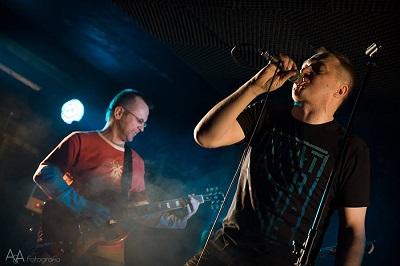 W tle mężczyzna gra na gitarze elektrycznej, zbliżenie twarzy mężczyzny z mikrofonem.