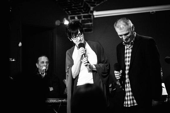 Na zdjęciu zespół muzyczny : mężczyzna gra na pianinie, przed nim stoją szczupła brunetka w okularach i szczupły mężączyzna w średnim wieku. Śpiewają .