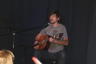 Mężczyzna na scenie, gra na gitarze.