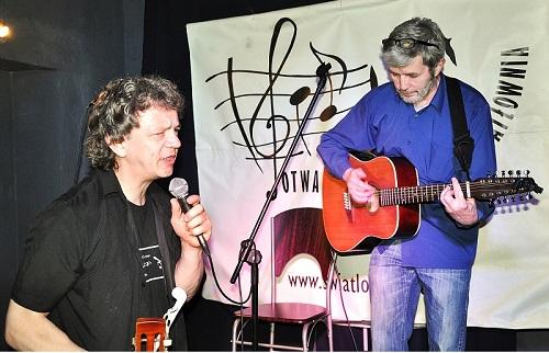 Na zdjęciu dwóch, szczupłych mężczyzn w średnim wieku. Jeden stoi na scenie, drugi przed sceną mówi do mikrofonu.