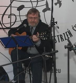 Na zdjęciu mężczyzna w średnim wieku, w okularach, na scenie, gra na gitarze i śpiewa. W tle logo Światłowni.