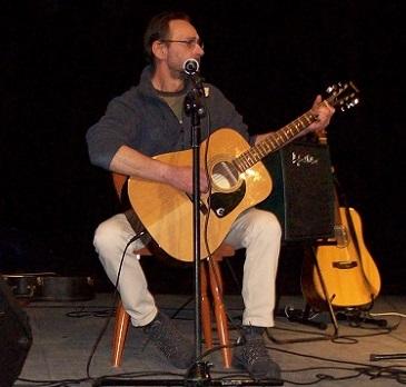 na zdjęciu młody, szczupły mężczyzna w okularach. Gra na gitarze.