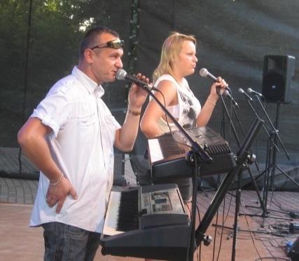 Nazdjęciu mężczyzna w średnim wieku, szczupły, z wyrażnymi zakolami, w białej koszuli śpiewa na scenie. Obok Kobieta w letniej sukience, blondyna, młoda, śopiewa do mikrofonu na statywie.
