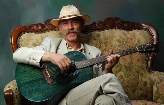 Na zdjęciu mężczyzna w średnim wieku, z wąsem, elegancko ubrany, siedzi na zabytkowej kanapie. Gra na gitarze klasycznej.
