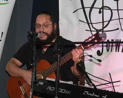 Młody mężczyna na scenie, gra na gitarze i śpiewa.