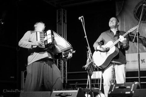 Dwóch muzyków(akordeonista, gitarzysta) w średnim wieku stoi na scenie
