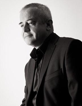 Na zdjęciu mężczyzna w średnim wieku, w garniturze.