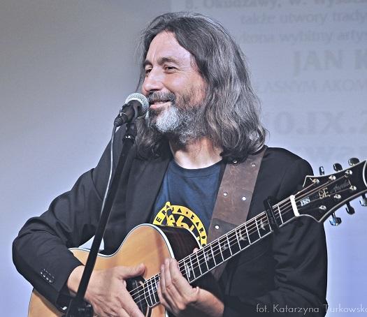Na zdjęciu mężczyzna z gitarą.