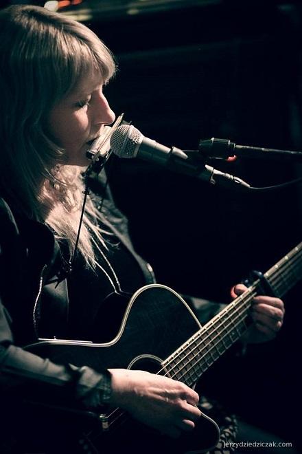 Kobieta gra na harmonijce ustnej i gitarze.