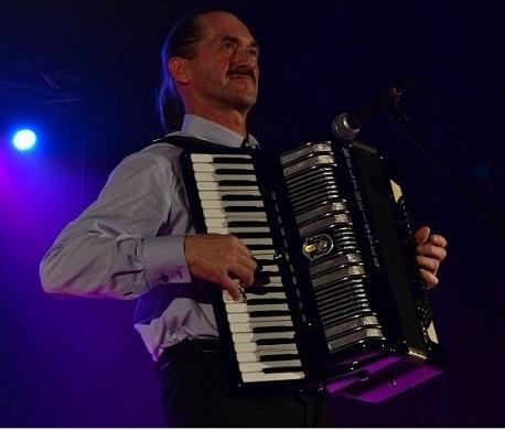 Na zdjęciu szczupły mężczyzna w średnim wieku. Gra na akordeonie.