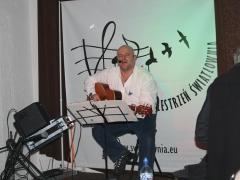 Na zdjęciu mężczyzna w białej koszuli, łysy, na scenie,gra na gitarze, śpiewa.