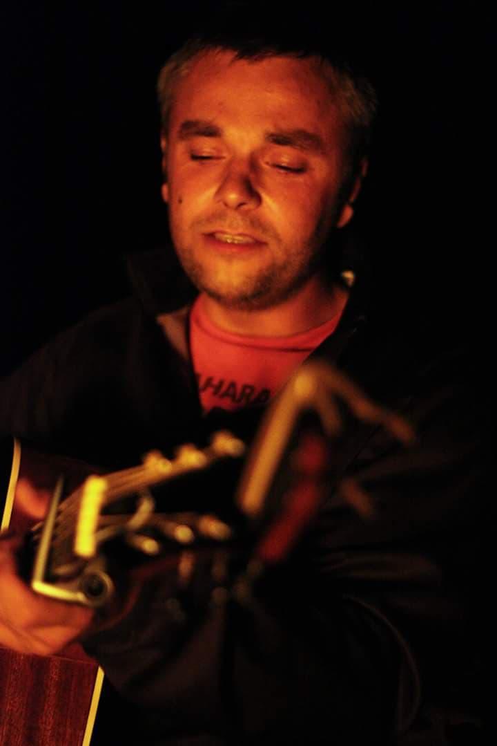 na ciemnym tle młody mężczyzna gra na gitarze klasycznej.