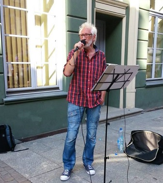 Wysoki, siwy mężczyzna w okularach śpiewa na ulicy.