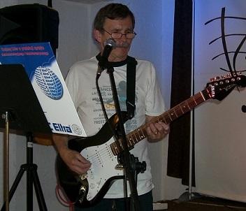 Na zdjęciu szczupły mężczyzna w średnim wieku, w okularach, stoi na scenie, gra na gitarze elektrycznej