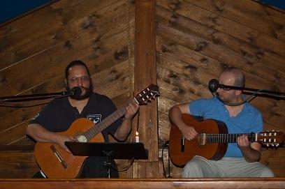 Na zdjęciu dwóch młodych mężczyzn siedzą na scenie, grają na gitarze i śpiewają. W tle ściana z boazerii.