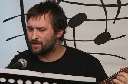 Na zdjęciu młody mężczyzna śpiewa i gra na gitarze.