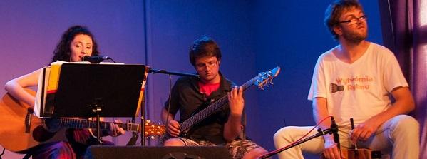Na zdjęciu troje młodych muyzyków: kobieta gra na gitarze, mężczyzna gra na gitarze elektrycznej, mężczyzna gra na cajon
