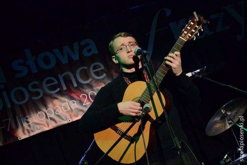 Młody mężczyzna , w okularach, na scenie, gra na gitarze klasycznej.