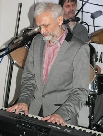 Na zdjęciu szczupły mężczyzna gra na pianinie cyfrowym.