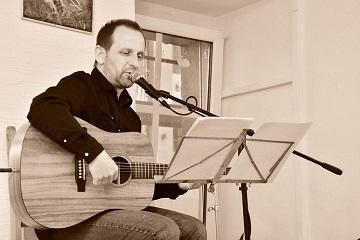 Mężczyzna na scenie, gra na gitarze klasycznej, śpiewa.