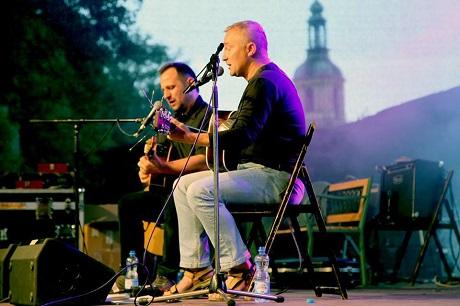 Dwóch mężczyzn na scenie, grają na gitarach. W tle kościół.