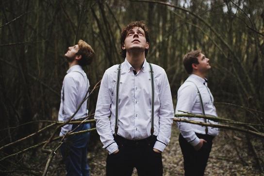 Trzech młodych mężczyzn w białych koszulach, stoją w lesie, patrzą w niebo.
