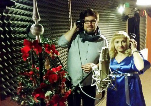 W scenerii świątecznej (choinka, bombki) młody mężczyzna, w okularach i młoda kobieta.