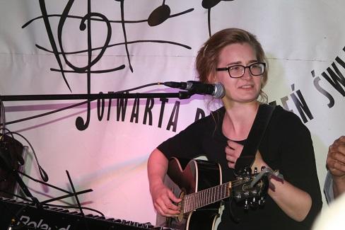 Młoda dziewczyna, w okularach, na scenie, gra na gitarze.
