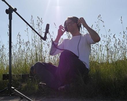 Na zdjęciu młody mężczyzna siedzi na łące, ma słuchawki na uszach. Przed nim statyw z mikrofonem.