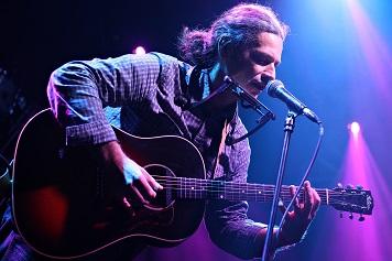 Młody mężczyzna, gra na gitarze.