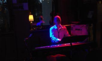 Młody mężczyzna w białej koszuli gra na keyboardzie.